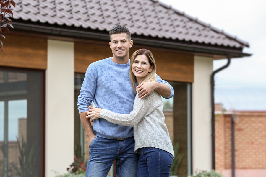 Personal Insurance - Happy Couple Standing in Front of Newly Purchased House